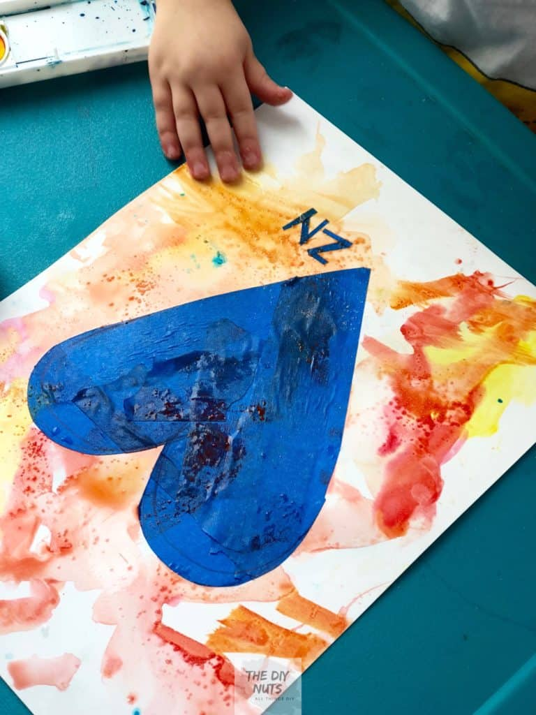 warm colored watercolor paint with child's hand painting heart and adding salt