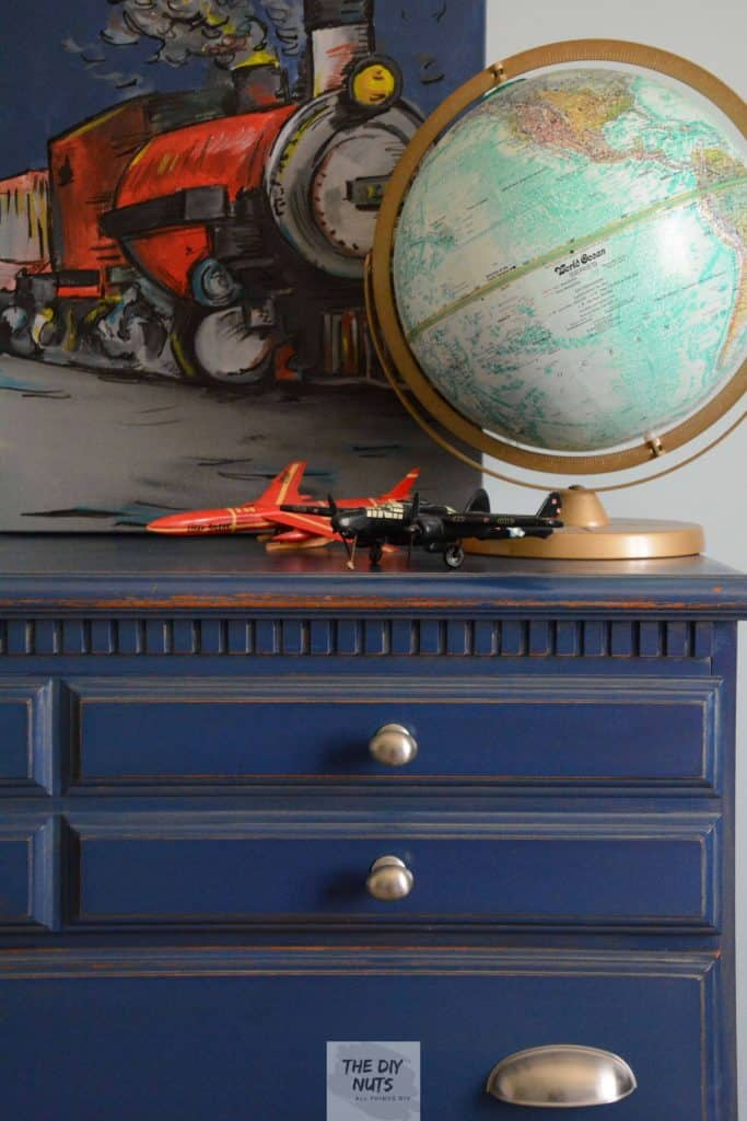 Blue Dresser with globe, small model planes and train artwork