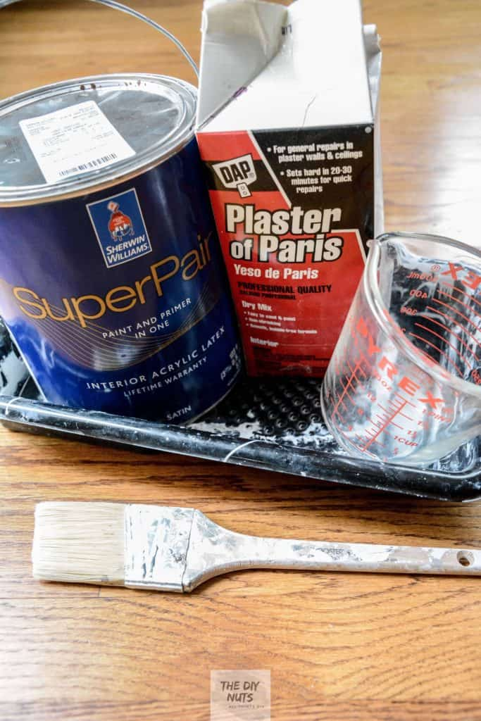 Plaster of paris, latex paint, paint tray, measuring cup and paint brush