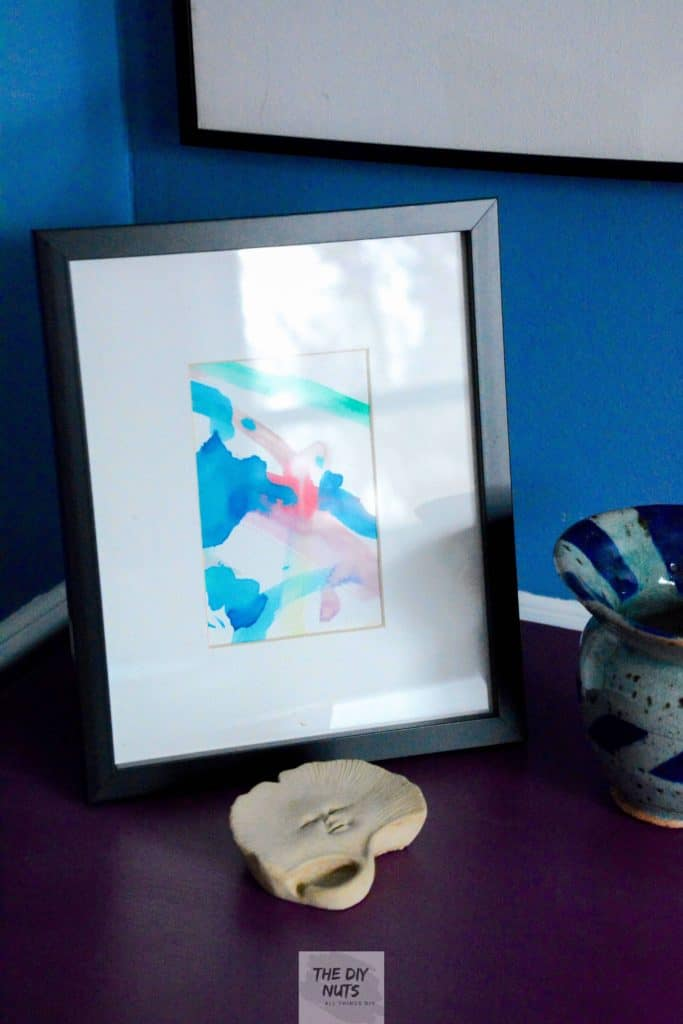 Small abstract watercolor painting made by toddler in black frame with white mat for a DIY easy artwork display