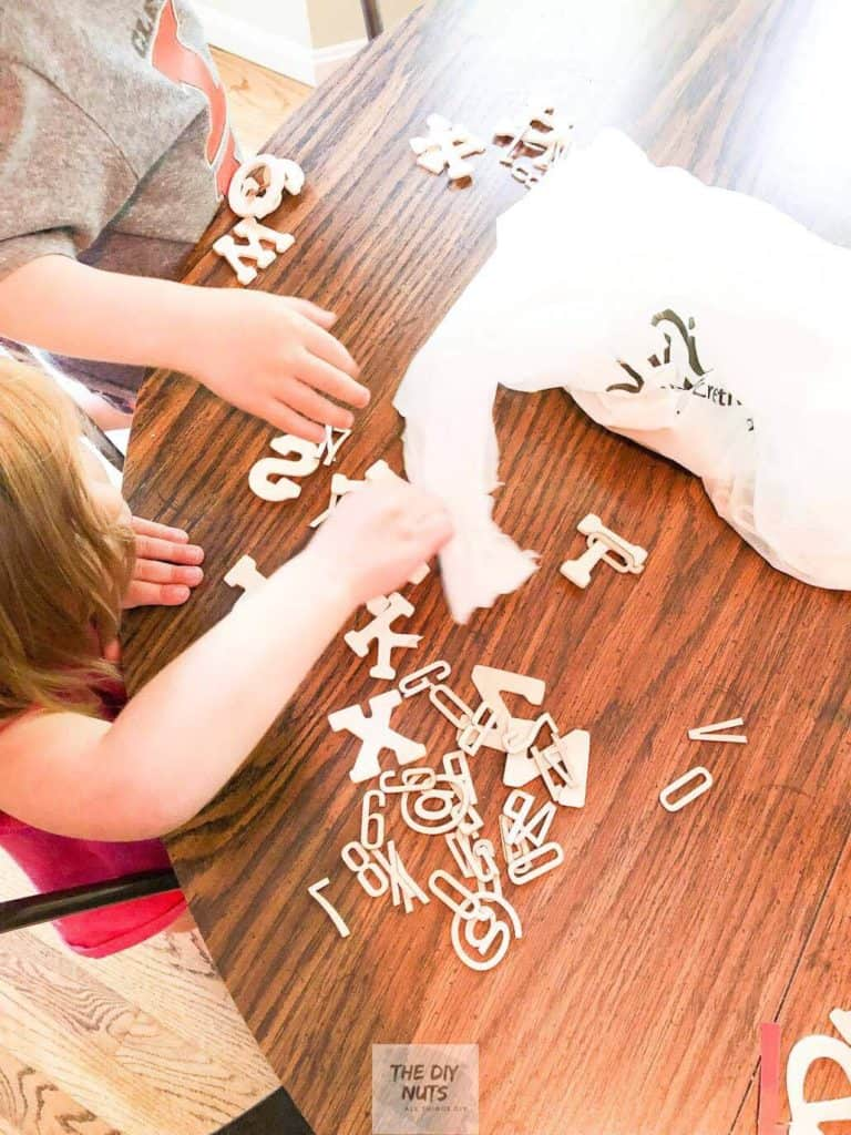 Toddlers picking out wooden letters