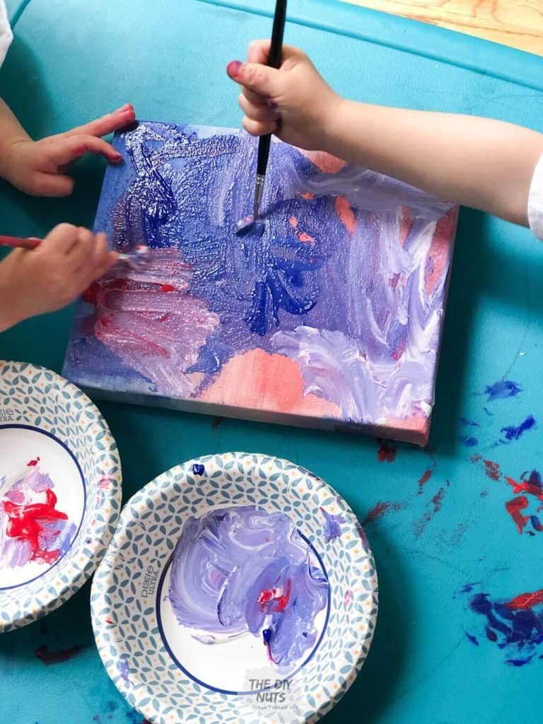 Two toddlers painting canvas using red, blue and white paints