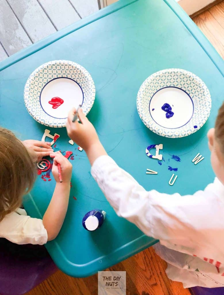 Children painting wooden letters for DIY word art canvas project