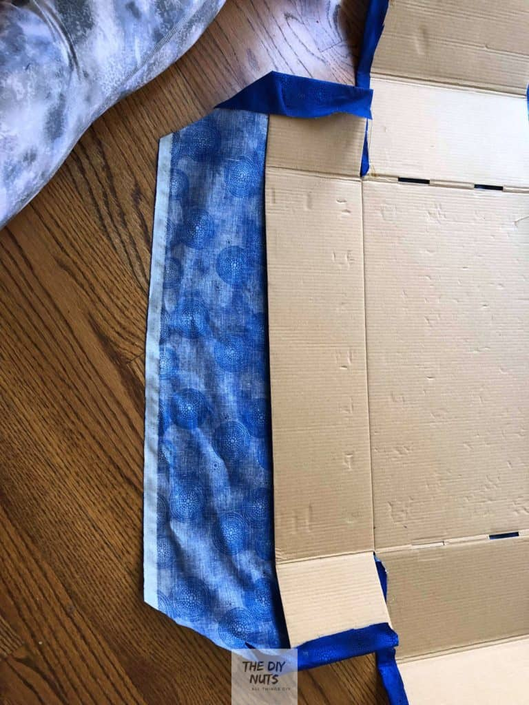 Cardboard box opened up on top of fabric
