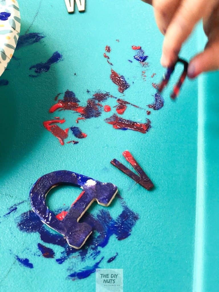 Child painting wooden letter for DIY word art