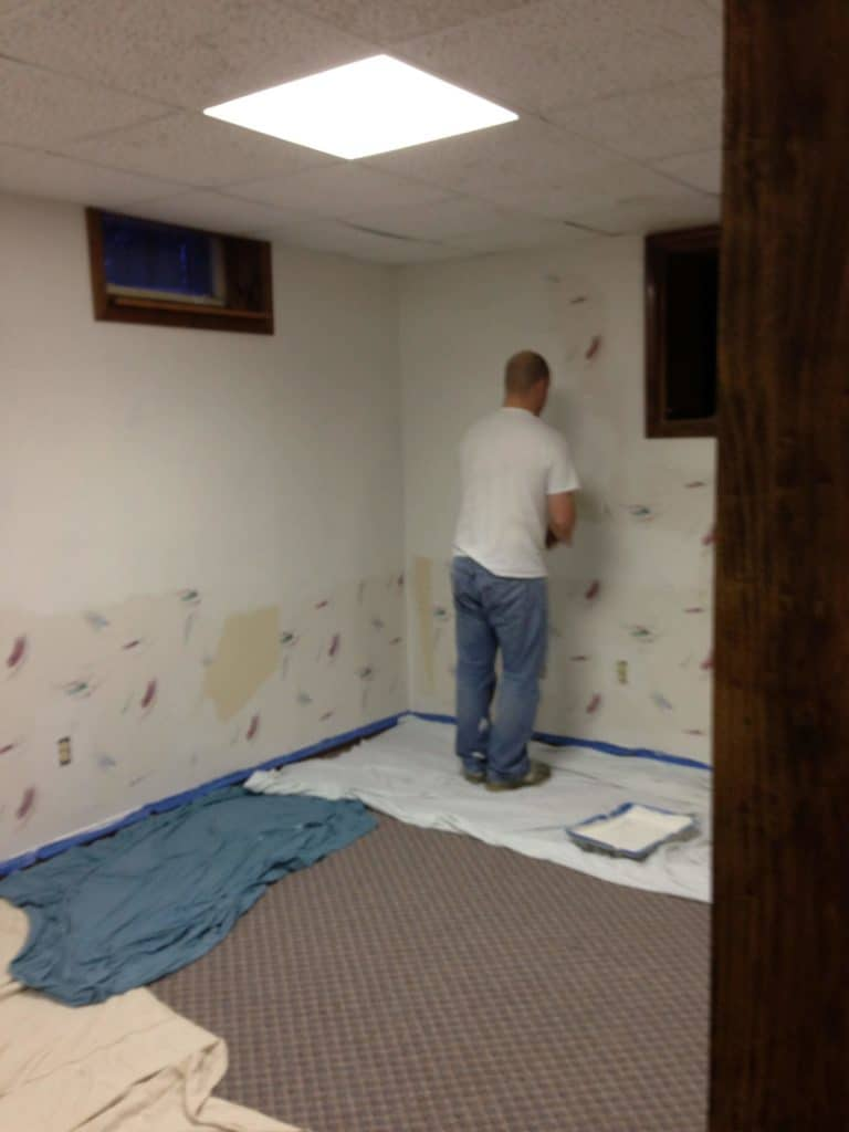 Man using wallpaper sealer on top of old wallpaper before painting