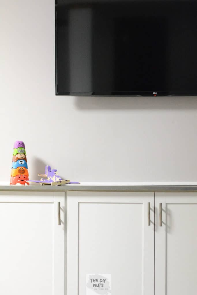 DIY Basement Makeover using white cabinets to create DIY built-ins below tv