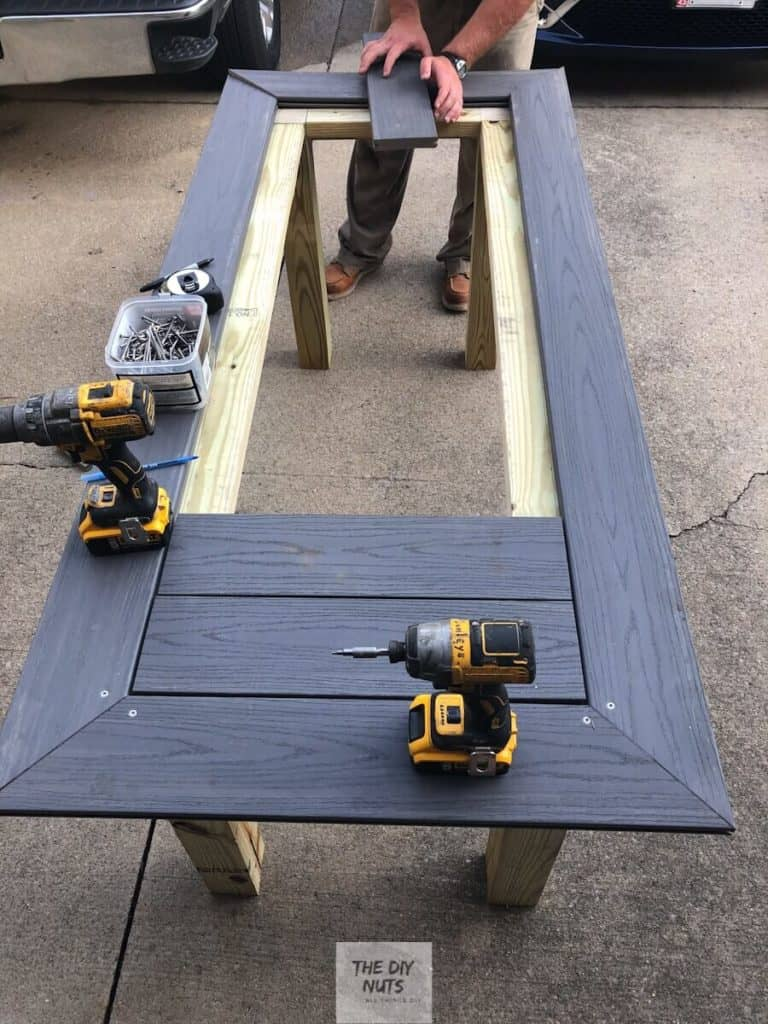 Smaller gray composite decking placed inside mitered table top frame on pressure treated wood base