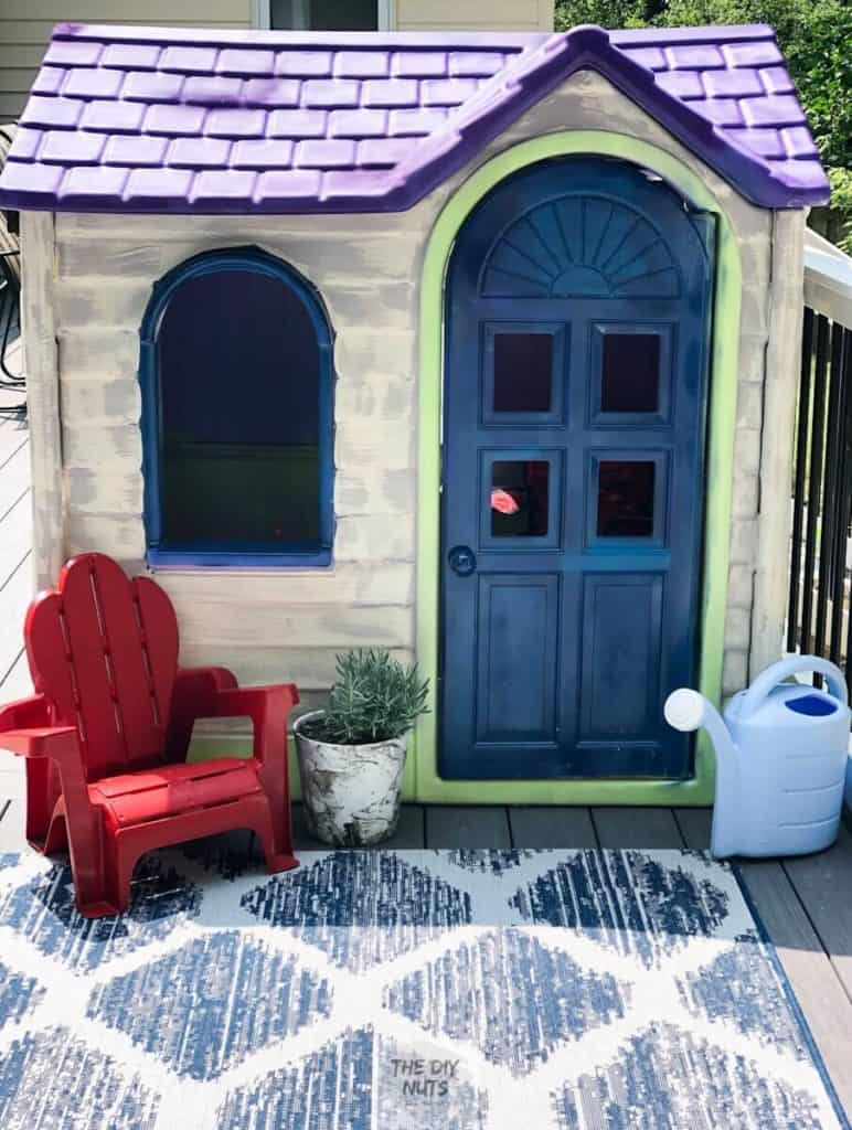 Blue, cream and purple little tykes playhouse with small red chair and marbled pot with plant