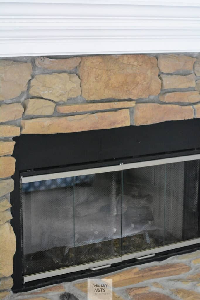 Silver metal and black fireplace cover and DIY white painted mantel with brown stone fireplace