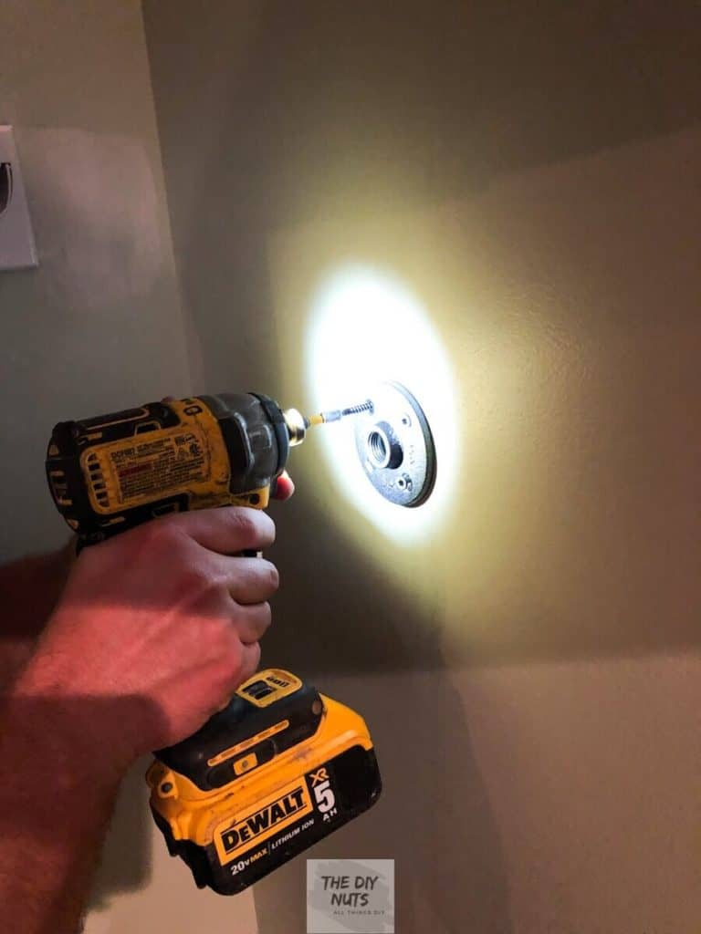 Handheld drill screwing in flanges to wall