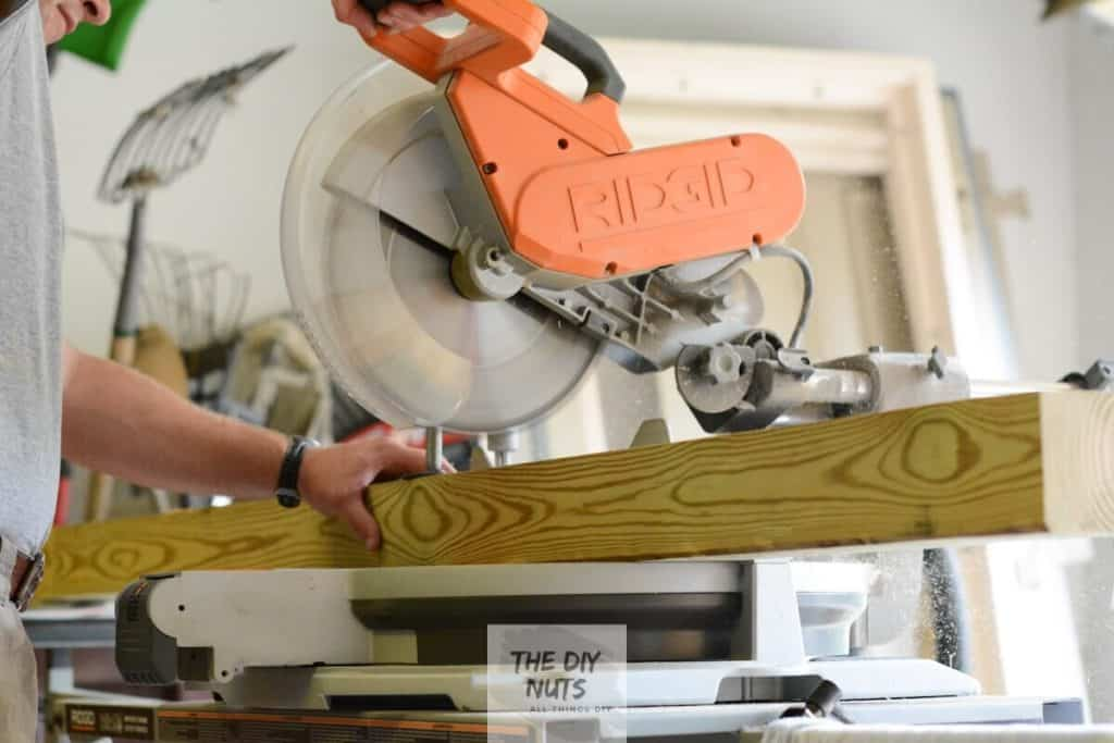 Using a saw to cut pressure treated wood for posts for DIY outdoor table