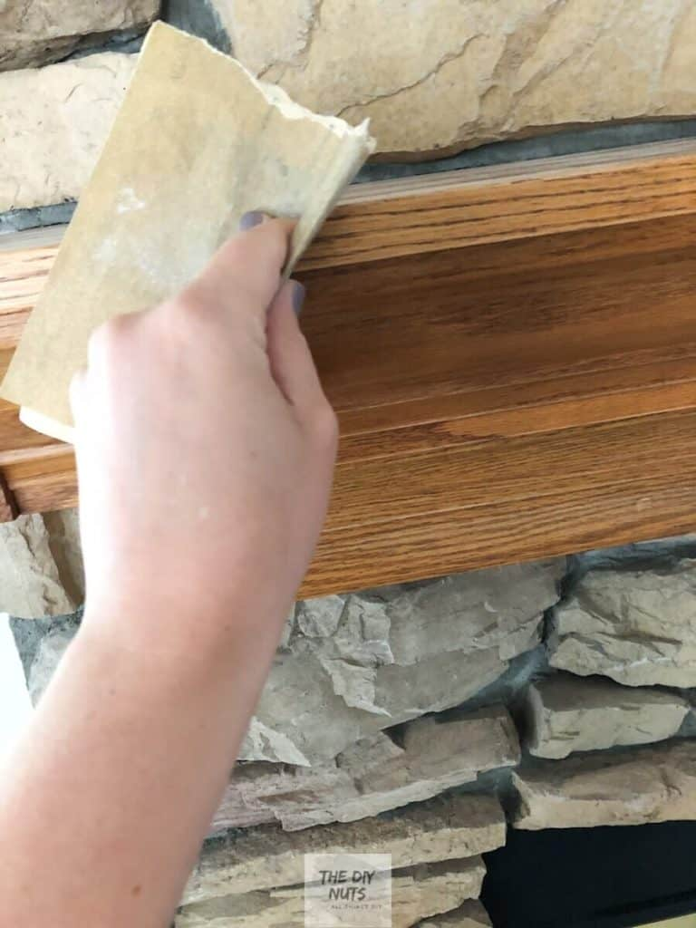 Fine sand paper being used to lightly rough up oak mantle before painting for DIY fireplace makeover