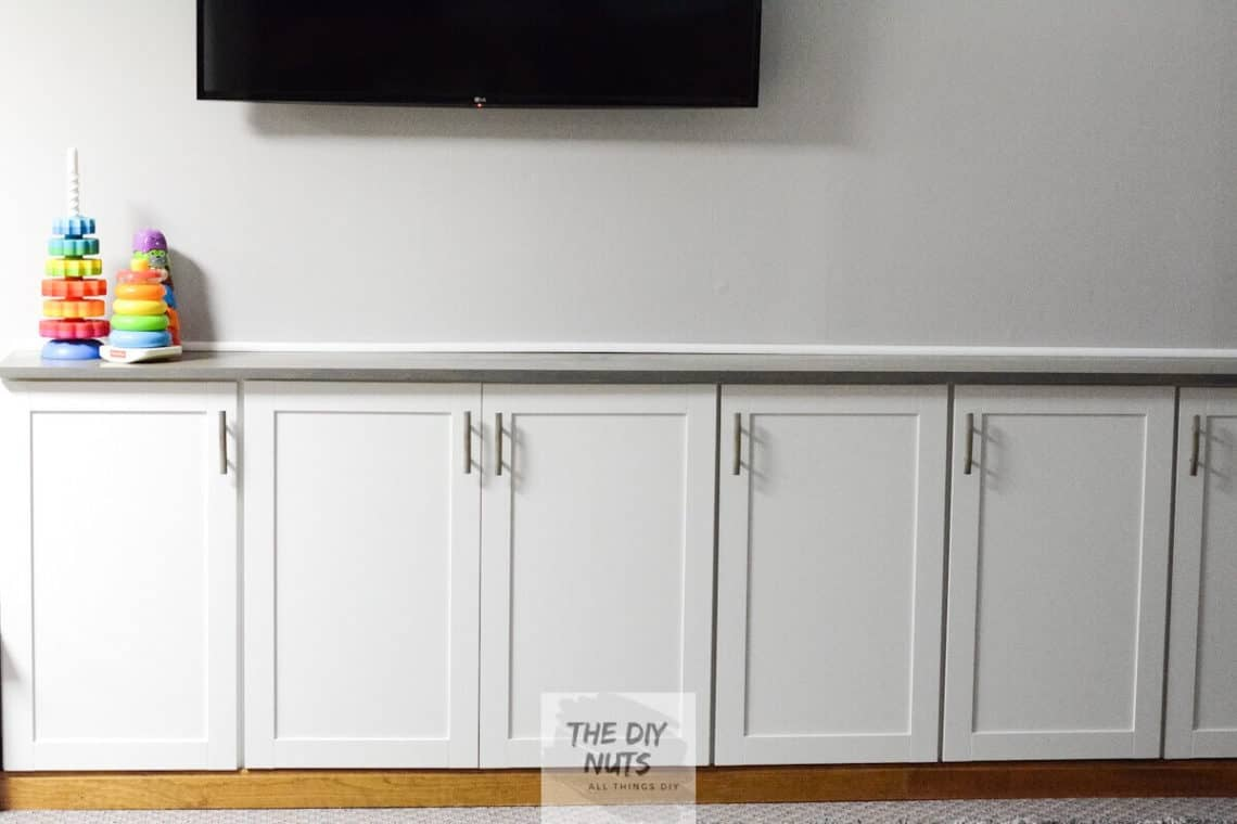DIY basement makeover with DIY storage cabinets using white upper kitchen cabinets