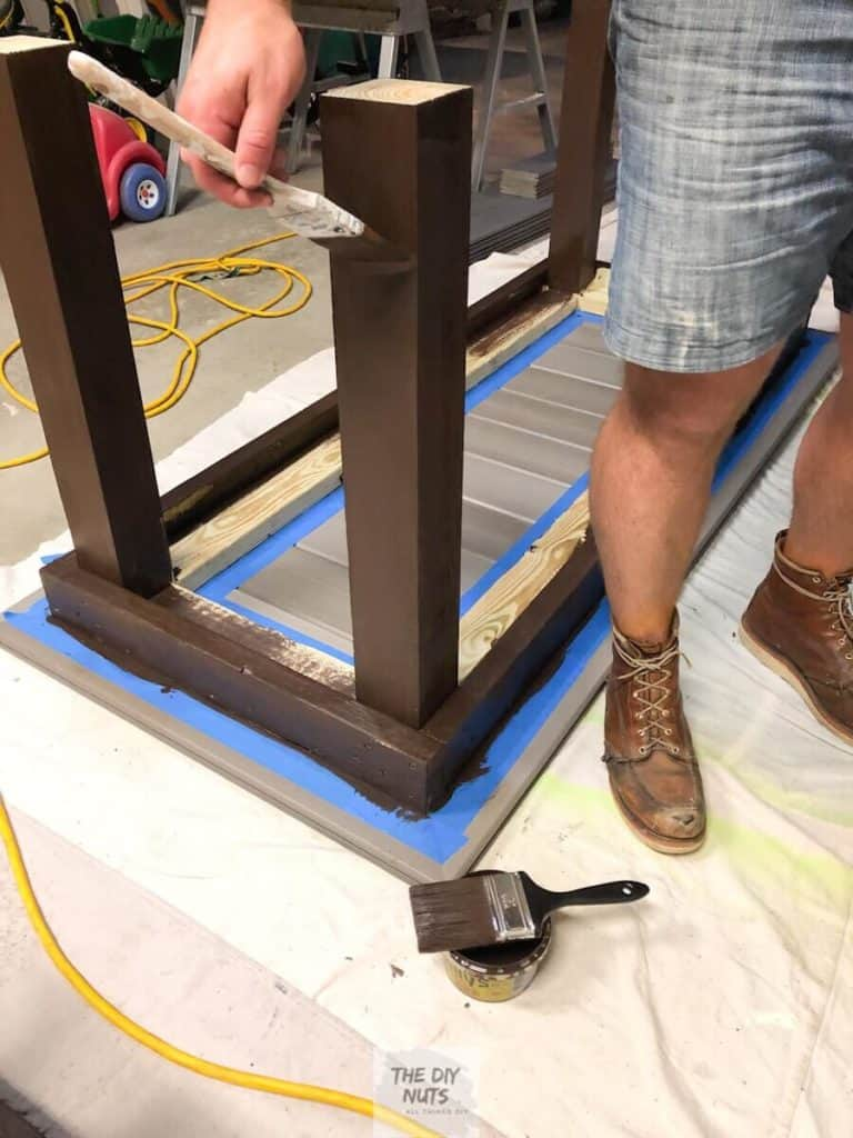 Dark brown exterior stain being applied to pressure treated outdoor table base