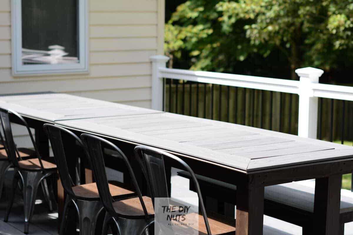 Large gray and DIY composite decking table with brown exterior stained legs with outdoor dining chairs