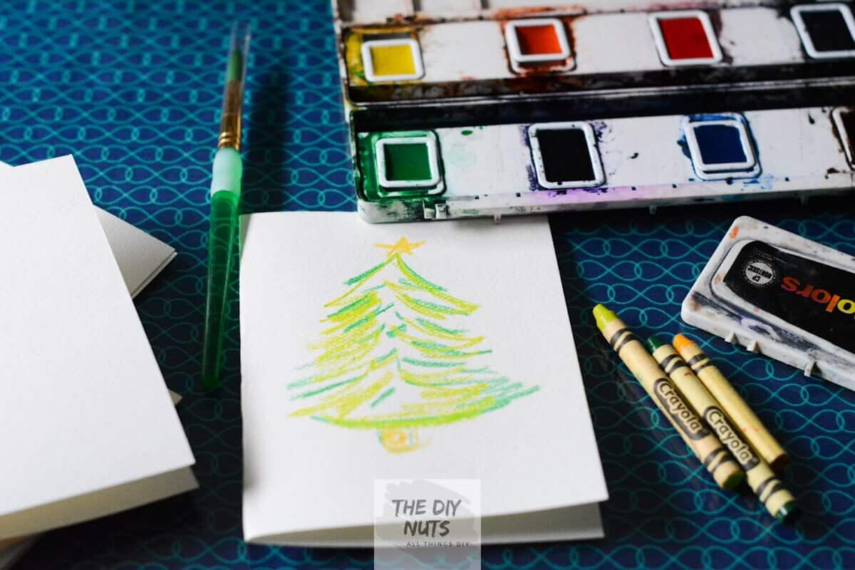 Watercolor paints, brushes and crayons with fold homemade holiday card with tree on it.