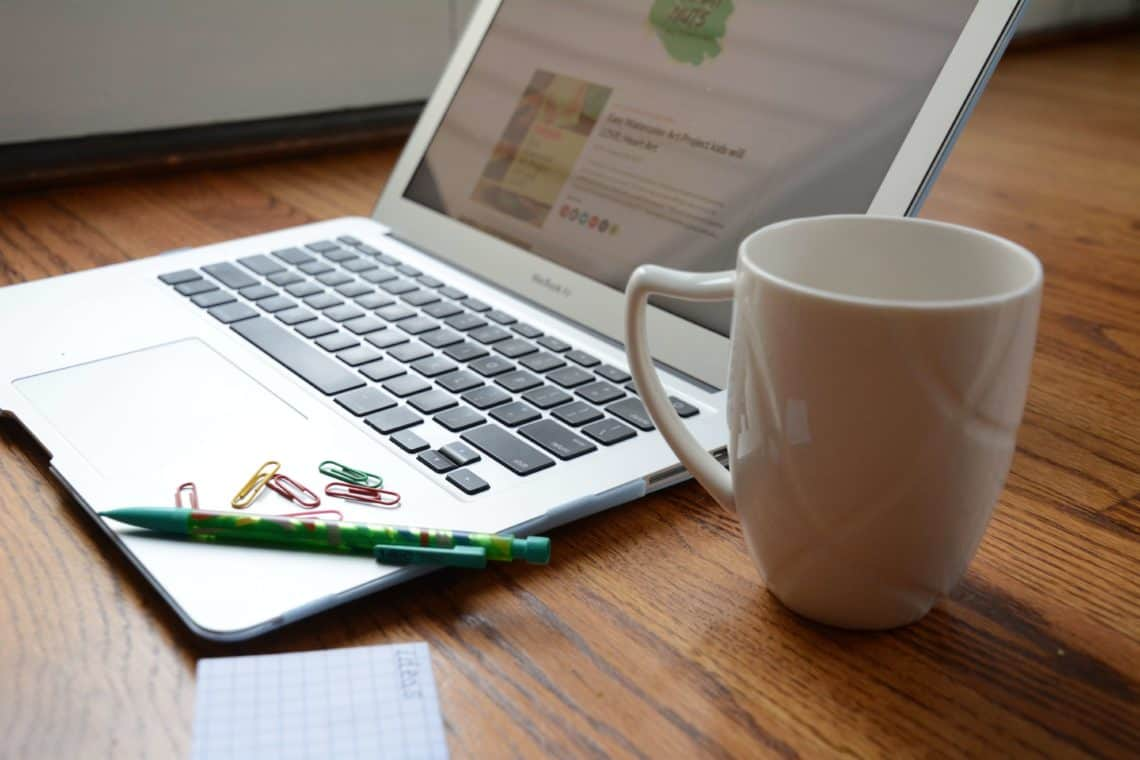 Computer with coffee cup, pencil and notepad to buy and sell things on Facebook