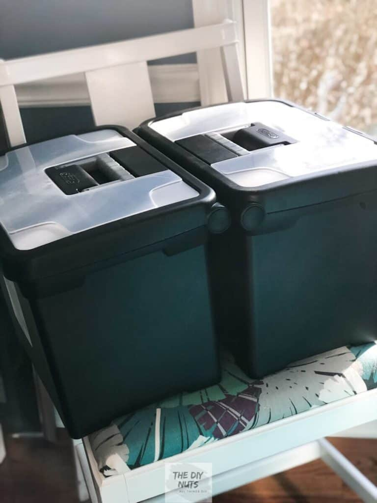 2 black plastic file containers sitting on chair