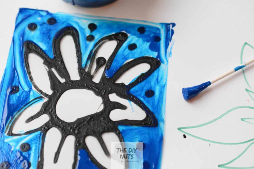 Blue paint with q-tip on transparency paper for stained glass project for kids