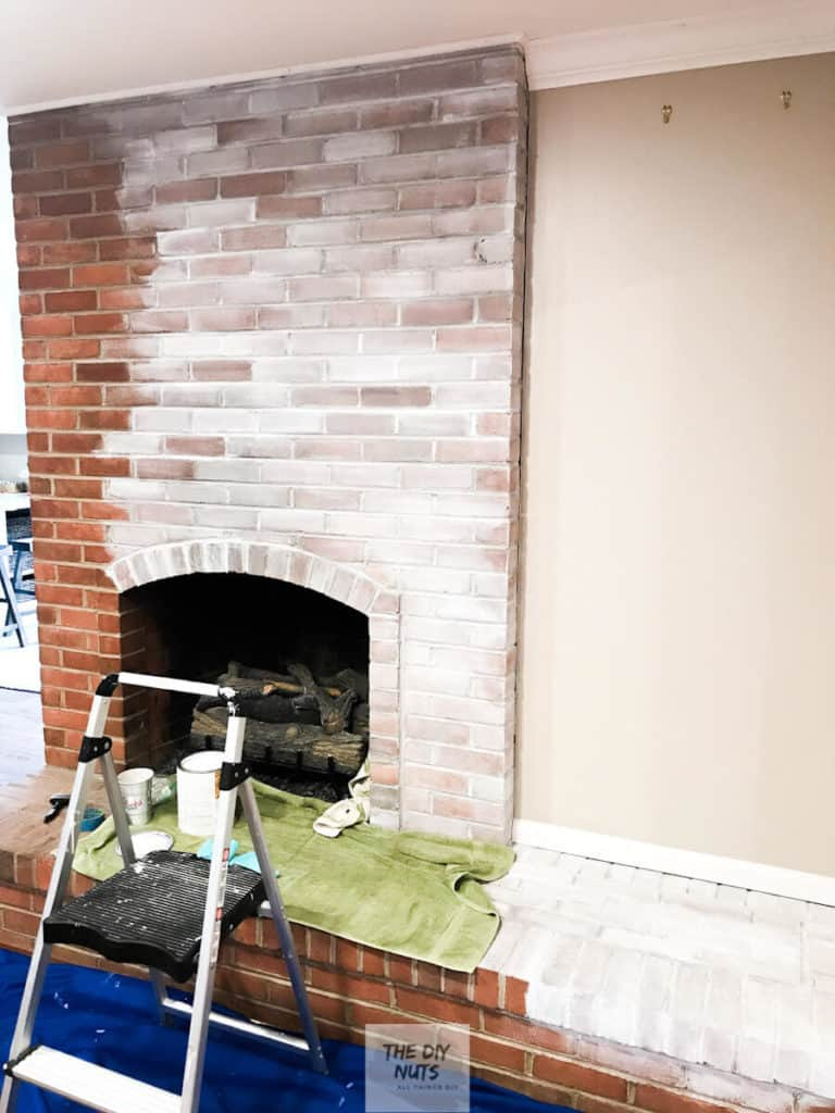 White paint being applied as DIY fireplace makeover idea