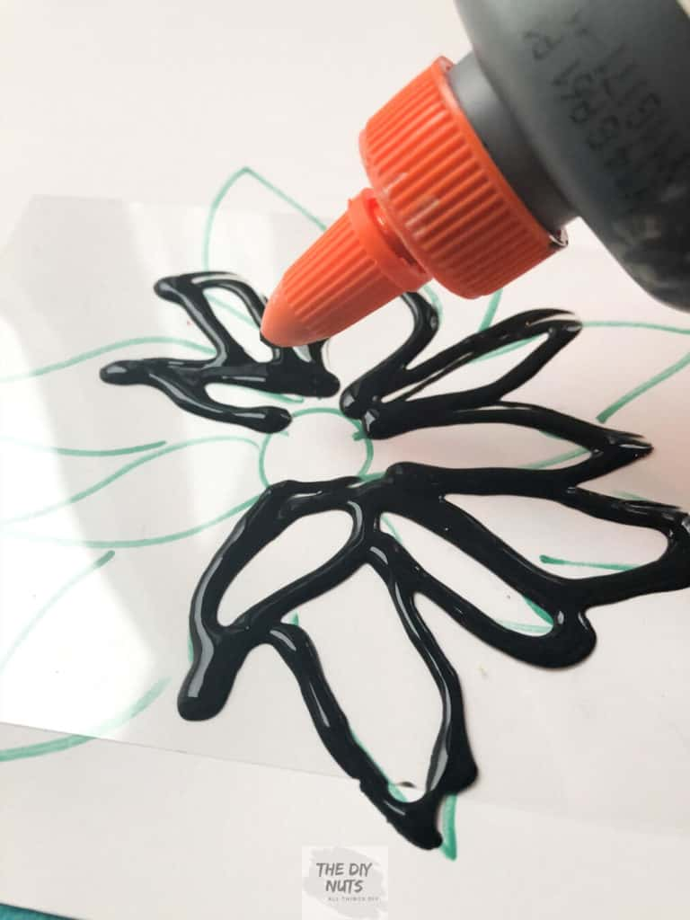 Black glue mixture being used to create a faux stained glass art project for kids
