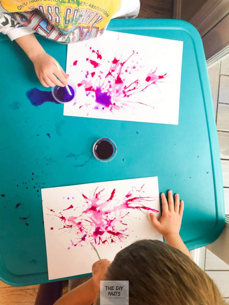 Jackson Pollock Inspired Paintings for Preschool-Aged Children blowing paint around on paper