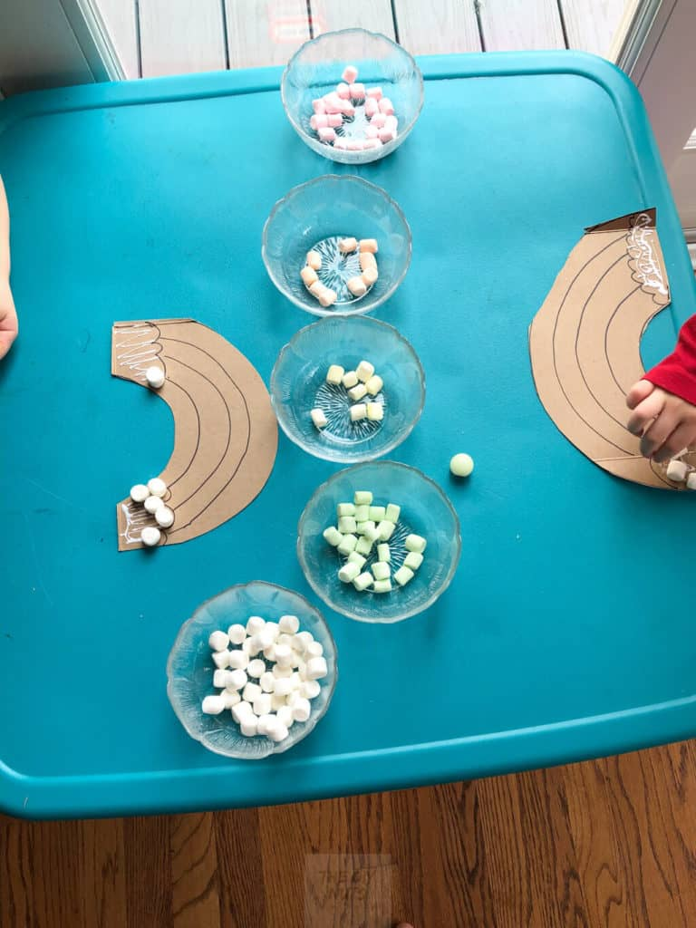 Toddlers gluing on marshmellows to rainbow craft