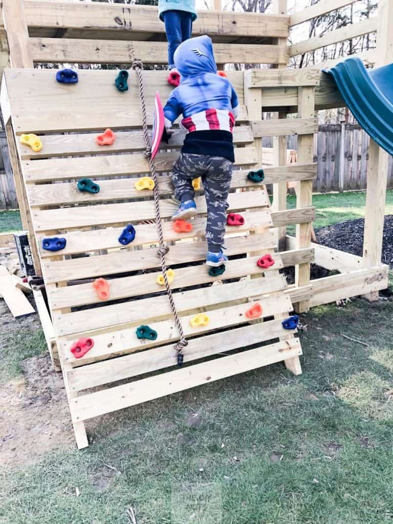 Child climbing DIY rock wall