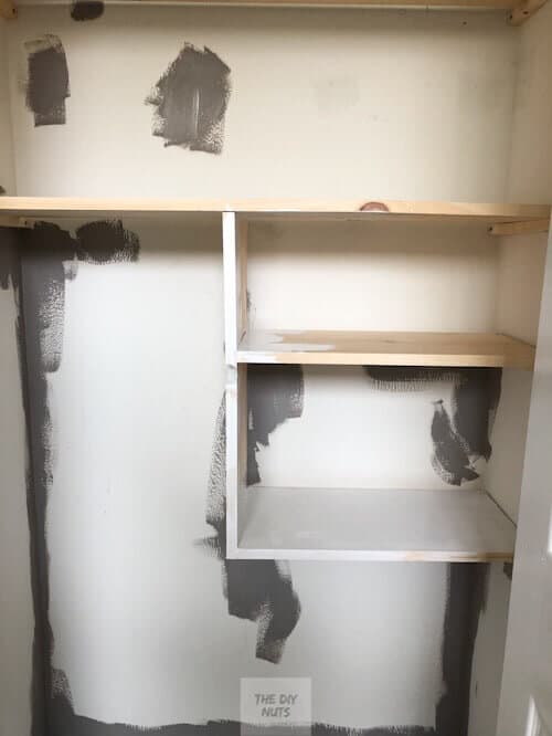 Wood shelving in small closet being painted