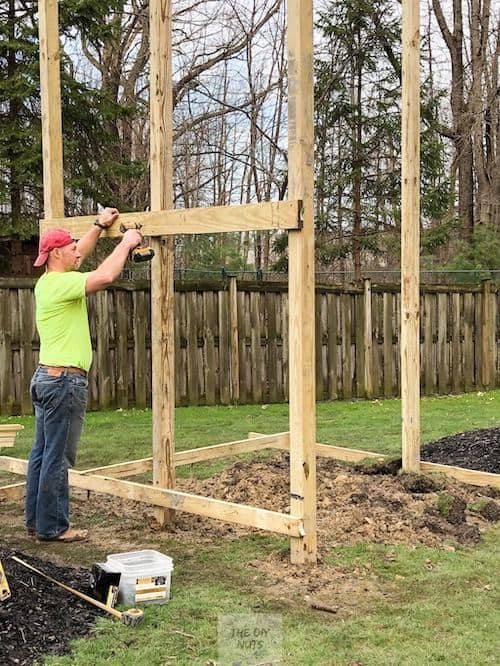 Man attaching 2 x 4 to posts