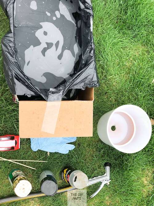 Box with garbage bag filled with water, spray paint, tape and terra cotta pot spray painted white