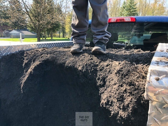 Feet on pile of dirt used to fill garden beds