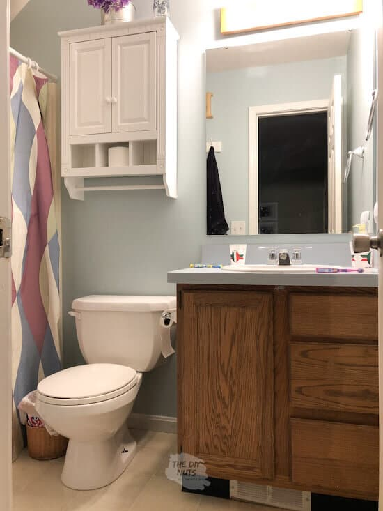 Dated oak cabinet vanity in small bathroom