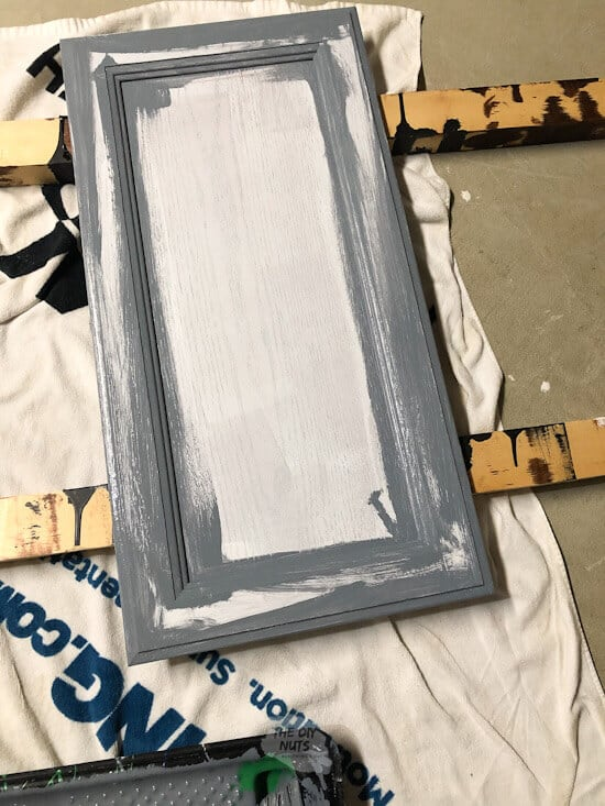 Using a paint brush to add gray latex enamel paint to cabinet door