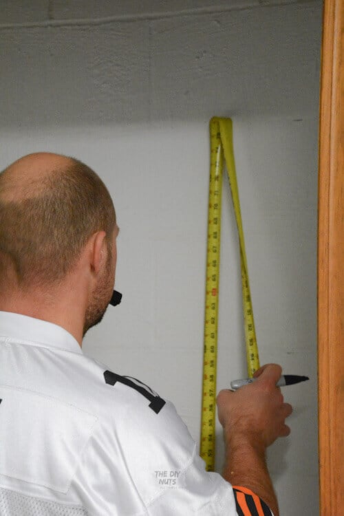 Using a tape measure to mark distance for shelving