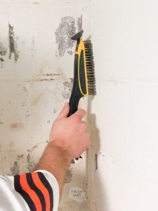 Use a wire brush to clean cinderblock in basement