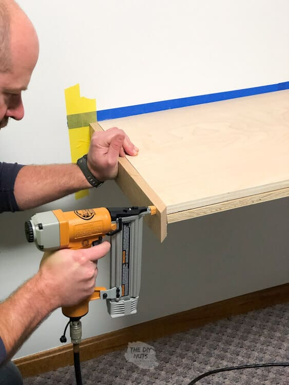 Brad nailer attaching oak trim to floating desk