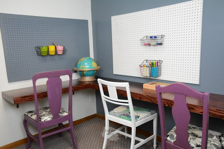 Floating corner desk with pegboards and repurposed chairs