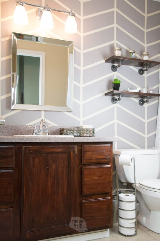 Herringbone painted wall in small bathroom with gel stained vanity