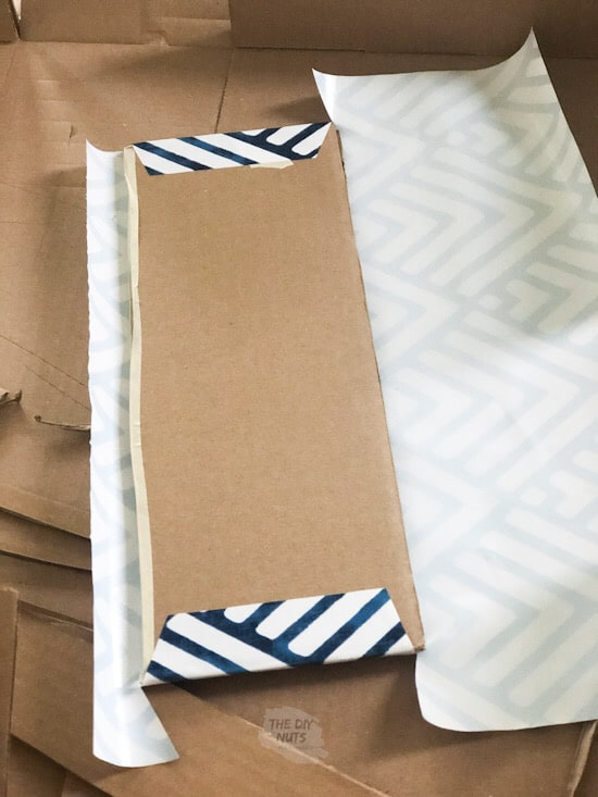 cardboard shelf being wrapped in contact paper