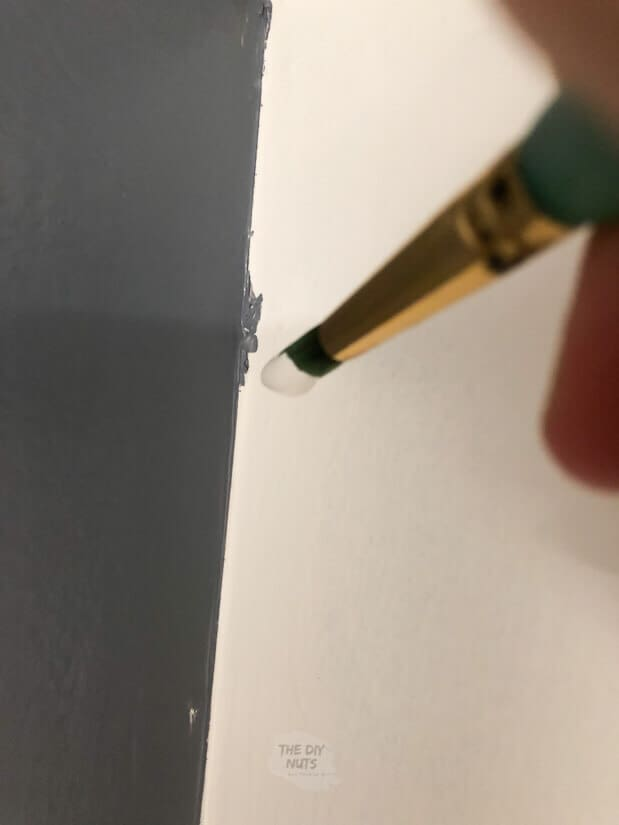 small brush touching up white paint with charcoal blue accent wall