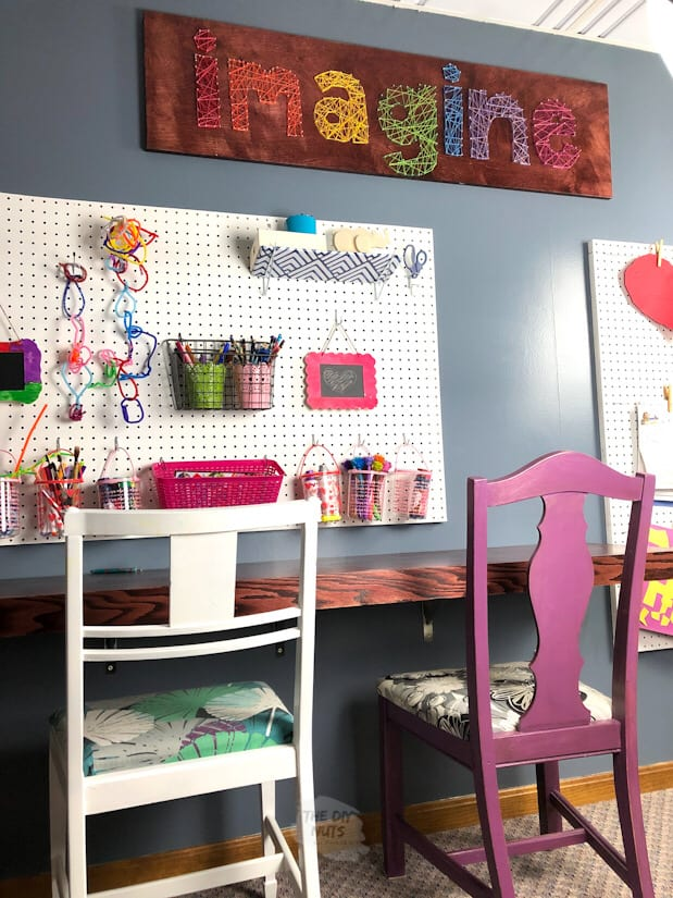 homeschool room with floating desk, white chair, purple chair, pegboard and large word art