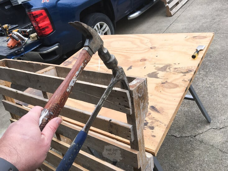 Two claw hammers break apart a pallet