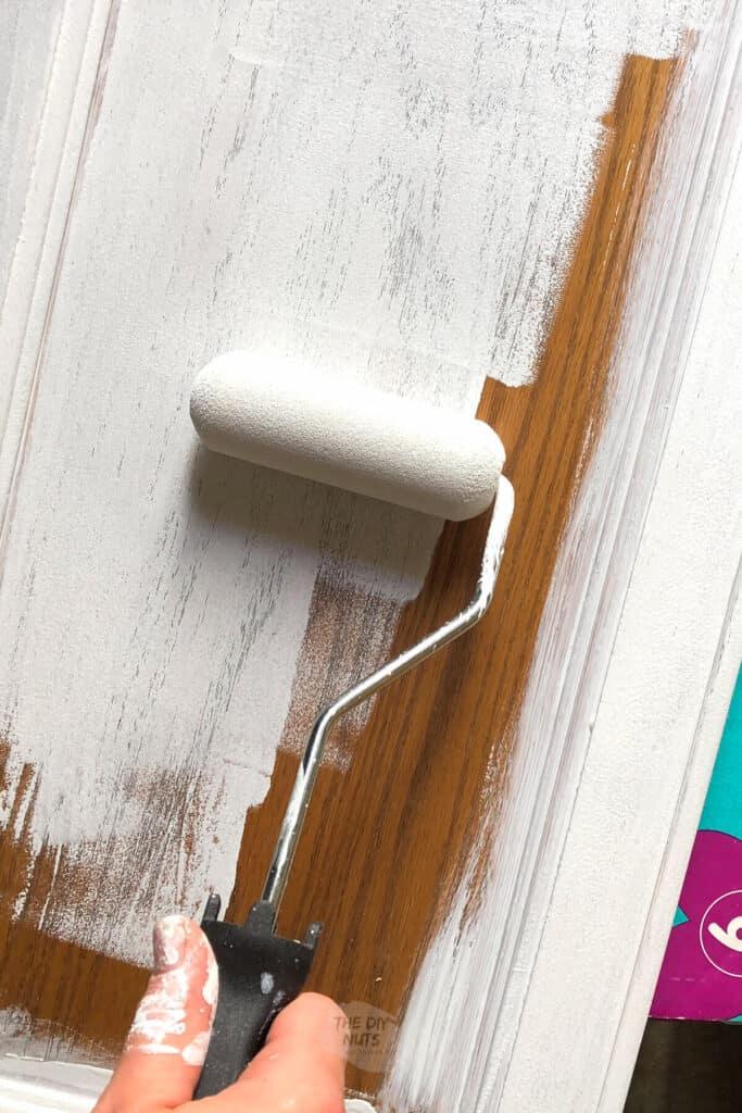 small foam roller applying latex primer to oak cabinet door