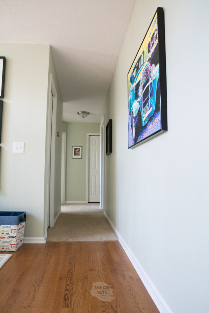 Sherwin Williams Livable Green Paint in hallway with painting and oak floors