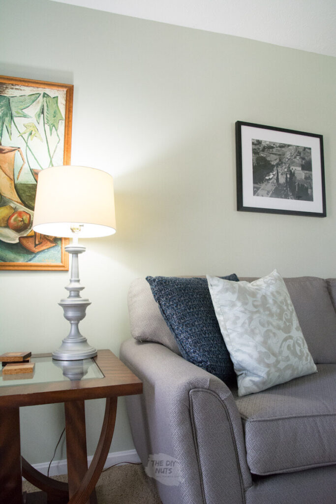 lamp on with painting and gray couch and liveable green painted walls