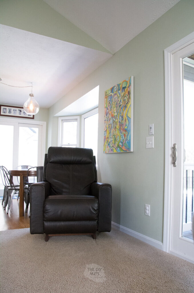 Liveable green walls with leather brown chair and white molding