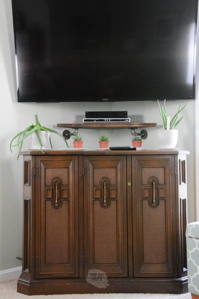 brown cabinet under corner mounted tv with DIY corner wall shelf