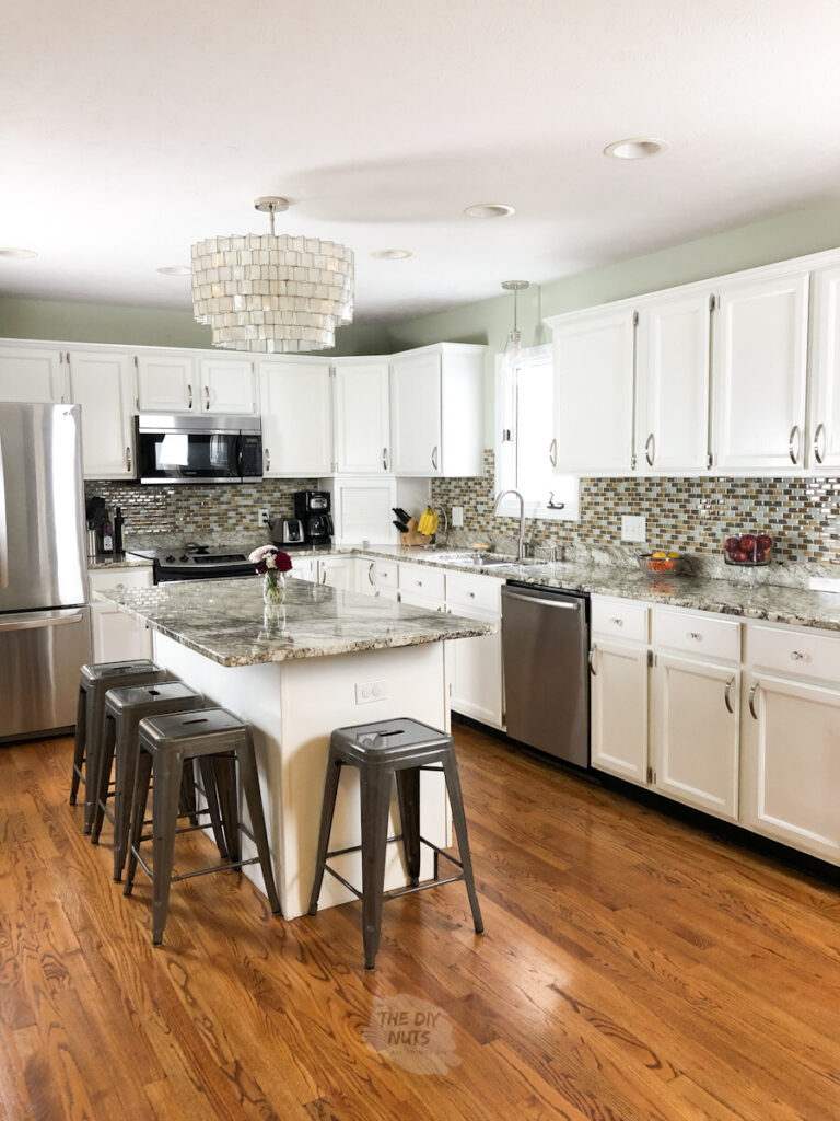 White painted kitchen cabinets with gray stools and light neutral green painted walls